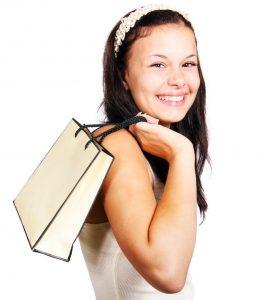 Eine junge Frau trägt eine Einkaufstüte über der Schulter und lacht